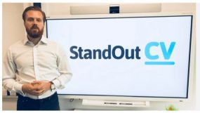 Photo of a man standing next to a TV screen showing the Standout CV logo